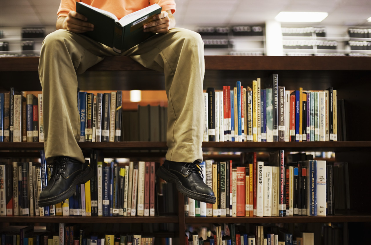Man Reading Book and Sitting on Bookshelf in Library - The Custom Luxury  Packaging Experts